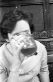Min (Rosemary Harvey) drinking