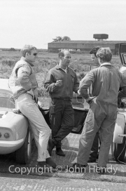 Stirling Moss & John Whitmore (in sunglasses). Moss tested for Lotus in 1963, after recovering from his 1962 crash at Goodwood, but retired without racing again.