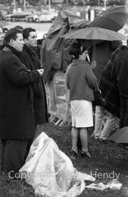 Spectators huddled under an umbrella