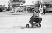 Stirling Moss on a scooter in the paddock