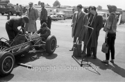 Formula Junior car stripped, with onlookers