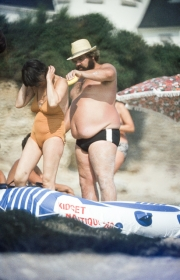 Fat Frenchman applying suncream to his partner