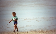 Small child on the beach, with ball