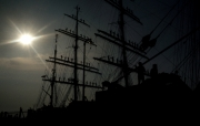 Russian tall ship manning the yards, against the sun