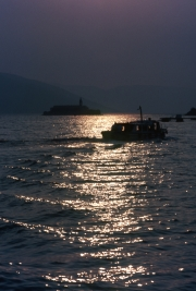 Sun track across the water, with boat and Monastery